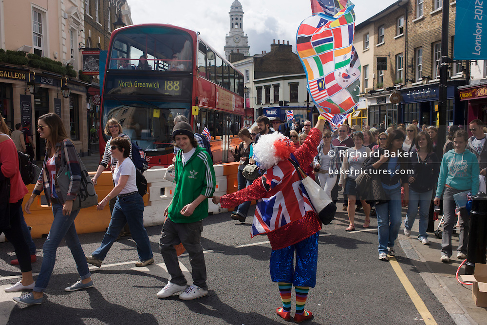 A clown character from the arts group Simply Smiley Productions entertains arriving sports spectators, walking through the streets of Greenwich on day 4 of the London 2012 Olympic games.