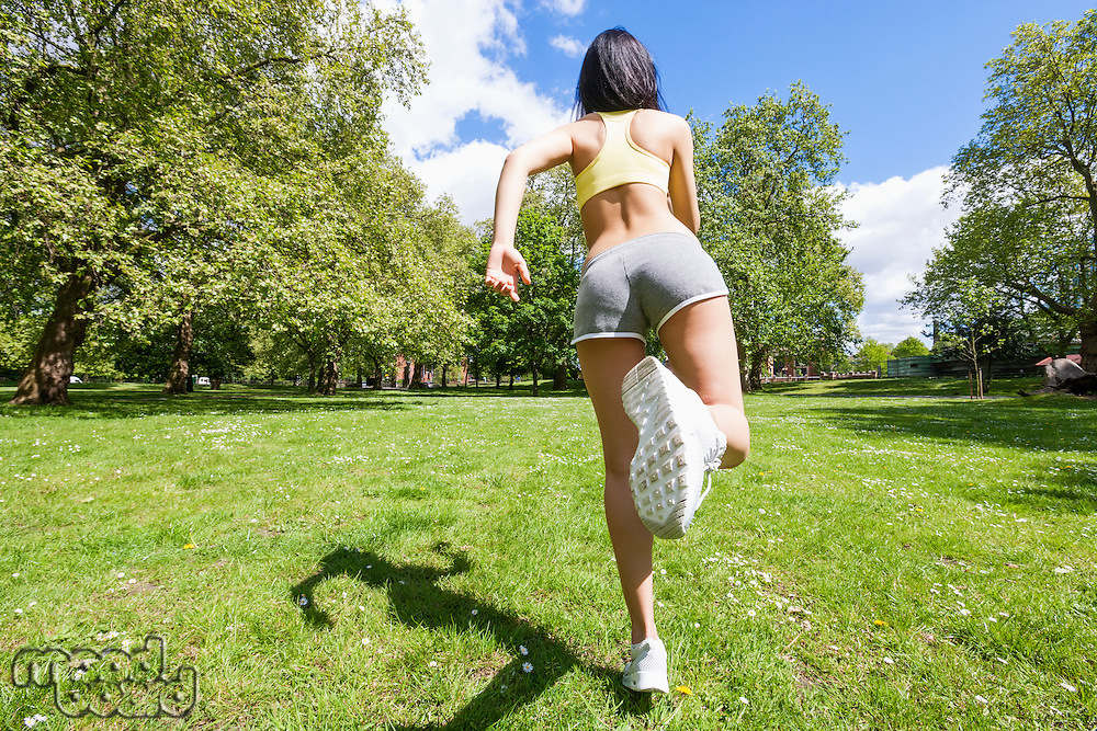 Full length rear view of fit woman jogging at park