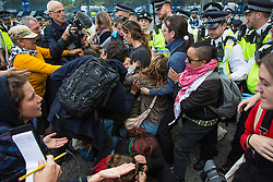 London, UK. 7 September, 2019. A very young child holds on to his mother as Metropolitan Police officers attempt to force back activists blocking the road in front of a truck attempting to deliver to ExCel London during the sixth day of Stop The Arms Fair protests against DSEI, the world's largest arms fair. The sixth day of protests was billed as a Festival of Resistance and included performances, entertainment for children and workshops as well as activities intended to disrupt deliveries to ExCel London for the arms fair.