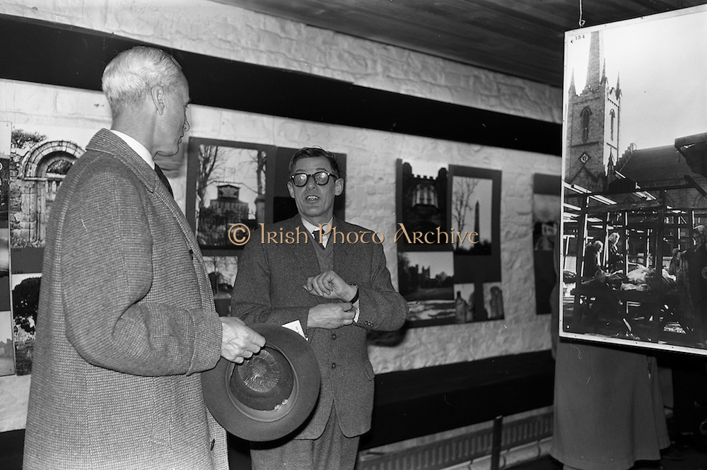 """05/04/1963<br /> 04/05/1963<br /> 05 April 1963<br /> Opening of """"Ulster Today"""" architectural photographic exhibition.Organised by the Royal Society of Ulster Architects opened at the Gallery of the Building Centre of Ireland  in Dublin in the presence of Donagh O'Malley, Parlimentary Secretary to the Minister for Finance and Sir Ian MacLennan, British Ambassador to Ireland. The exhibition was later displayed in Belfast. Picture shows: Dr. R.B. McDowell, Trinity College, Dublin, who officially opened the exhibition (right) discussing the exhibition."""