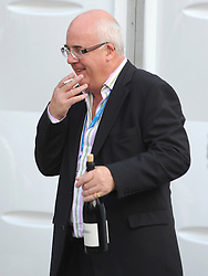 © Licensed to London News Pictures. 03/10/2011. MANCHESTER. UK. A delegate smokes and carries a bottle of wine at The Conservative Party Conference at Manchester Central today, October 3, 2011. Photo credit:  Stephen Simpson/LNP