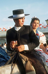 Couple riding on horseback at the Seville Spring Fair; with the man drinking sherry,