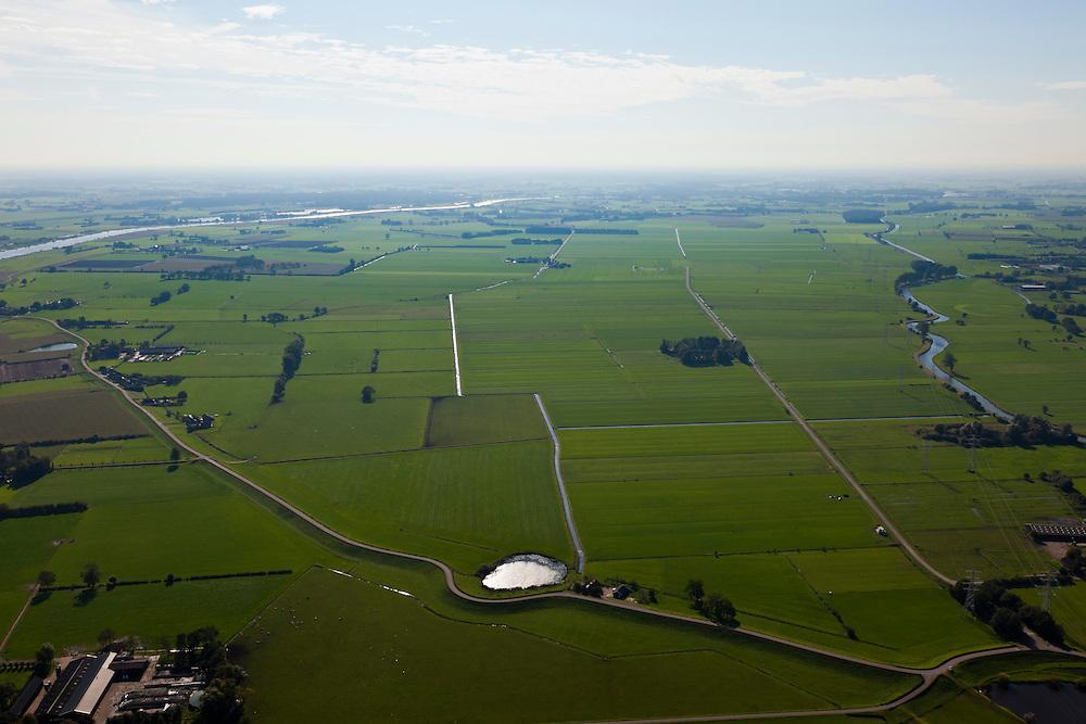 Nederland, Overijssel, Gemeente Heerde, 03-10-2010; landelijk gebied  ten westen van de IJssel (links), voorbestemd voor de aanleg van de toekomstige hoogwatergeul Veessen-Wapenveld. Foto naar het zuiden. De geul wordt niet gegraven maar ontstaat door twee dijken aan te leggen. Deze dijken beginnen aan weerszijden van de Kromme Kolk, (het meertje in de kromming van de dijk), op deze plaats ook de uitlaat van de geul. Het water rechts, de Grote Wetering, ligt naast de toekomstige westelijke dijk en blijft bestaan. .Rural area west of the IJssel (left), destined for the construction of future high-water channel Veessen Wapenveld. Photo to the south. .The channel will not be excavated but but instead two parallel dikes will be constructed. These dikes start on both sides of the Kromme Kolk, (the small lake in the curvature of the dike). Also at this point the outlet of the channel. .luchtfoto (toeslag), aerial photo (additional fee required).foto/photo Siebe Swart