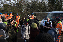 Harefield, UK. 8 February, 2020. A police officer speaks to environmental activists from Save the Colne Valley, Stop HS2 and Extinction Rebellion blocking a HS2 vehicle during action to prevent HS engineers from carrying out tree felling works for the high-speed rail project. The activists were successful in preventing any of the scheduled tree felling by HS2 and after an intervention by a police officer all tree felling work has now been cancelled for the weekend.
