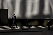A black gentleman walks along a sunlit corner of a City of London lane.