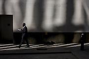 A black gentleman walks along a sunlit corner of a City of London lane.