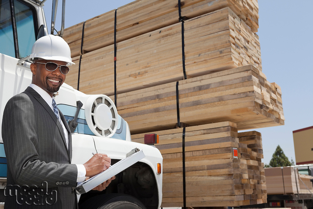 Portrait of African American male contractor writing notes while standing by logging truck