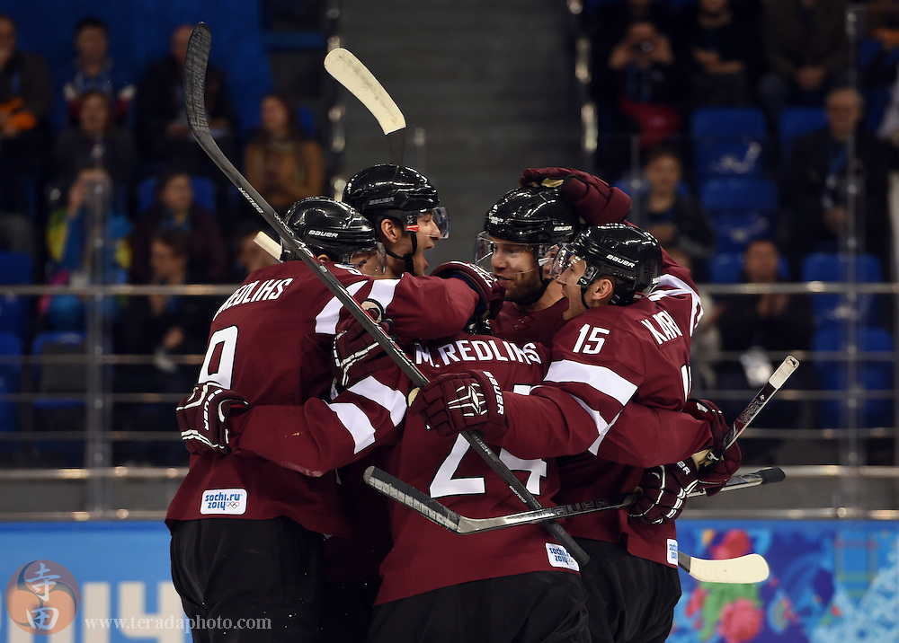 Feb 15, 2014; Sochi, RUSSIA; Latvia forward Janis Sprukts (5) celebrates with teammates after scoring a goal against Sweden in a men's preliminary round ice hockey game during the Sochi 2014 Olympic Winter Games at Shayba Arena.