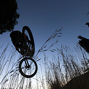 Malachi Artise gets air on his mountain bike at sunrise on Teton Pass near Wilson Wyoming. Parallel Trail.