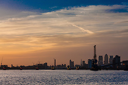 North Woolwich, London, October 28th 2014. London's skyline is silhouetted against a big sky as the autumn sun sets.