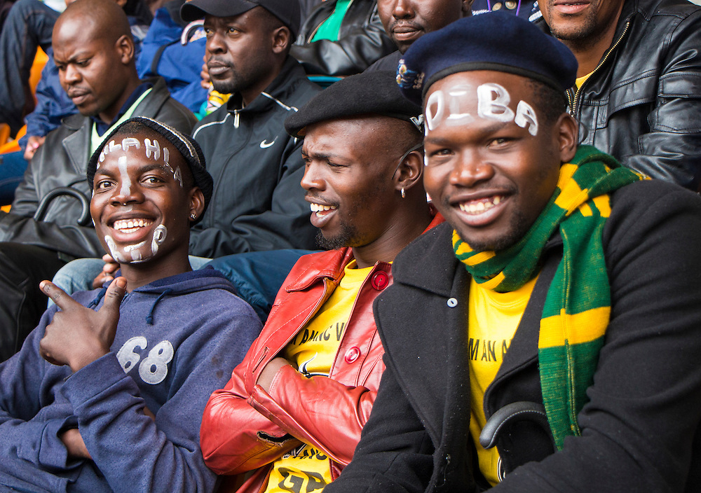 Young men with Nelson Mandela's clan and traditional name painted on their face attend the memorial service