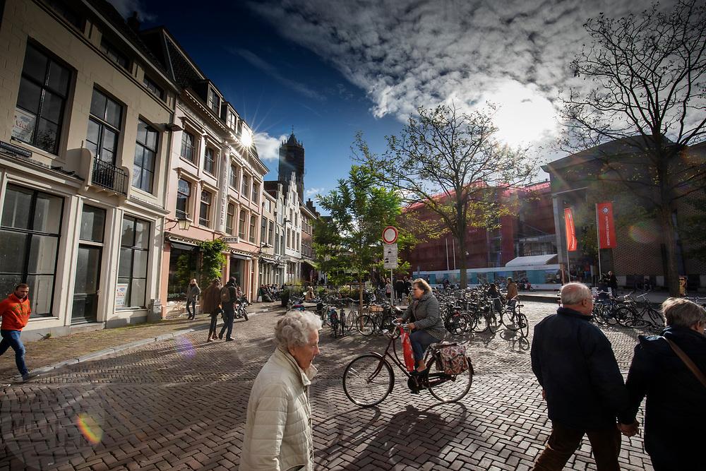 Mensen lopen en fietsen op een zonnige herfstdag in de binnenstad van Utrecht over de Korte Minrebroederstraat.<br /> <br /> People walk and cycle at the city center of Utrecht on a sunny autumn day.