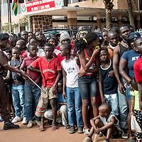 03/03/2014. Bissau. Guinée Bissau. Un agent de sécurité repoussent les nombreux spectateurs qui attendent le passage du défilé du Carnaval de Bissau où sont représentés les différentes régions et quartiers de la capitale. ©Sylvain Cherkaoui pour JA.