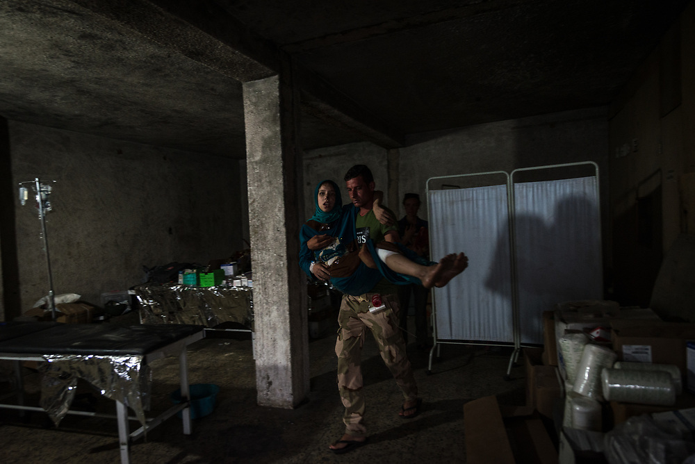 A soldier carries a frail woman to an ambulance after she received emergency treatment for hunger, dehydration and heat exhaustion at a trauma stabilisation point outside the Old City of Mosul.