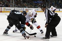 Jan 19, 2012; San Jose, CA, USA; NHL linesman Vaughan Rody (73) drops the puck on a face off to San Jose Sharks center Joe Pavelski (8) and Ottawa Senators center Jason Spezza (19) during the second period at HP Pavilion. Ottawa defeated San Jose 4-1. Mandatory Credit: Jason O. Watson-US PRESSWIRE