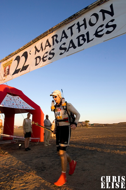 30 March 2007: A participant crosses the finish line during fifth stage of the 22nd Marathon des Sables between west of Kfiroun and erg Chebbi (26.22 miles). The Marathon des Sables is a 6 days and 151 miles endurance race with food self sufficiency across the Sahara Desert in Morocco. Each participant must carry his, or her, own backpack containing food, sleeping gear and other material.