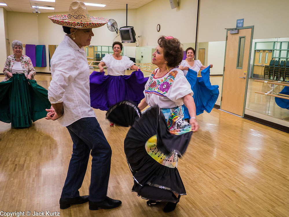 27 JUNE 2012 - GLENDALE, AZ:  SHENY RUIZ MILLIGAN, 67 years old, and HENRY ARBALLO, do a Mexican Hat Dance during rehearsal for the Senior Fiesta Dancers at the Glendale Adult Center, in Glendale, AZ, a suburb of Phoenix. Dancing as a part of workout regimen is not unusual, but the Senior Fiesta Dancers use Mexican style folklorico dances for their workouts. The Senior Fiesta Dancers have been performing together for 15 years. They get together every week for rehearsals and perform at nursing homes and retirement centers in the Phoenix area once a month or so. Their energetic Mexican folklorico dances keep them limber and provide a cardio workout.   PHOTO BY JACK KURTZ