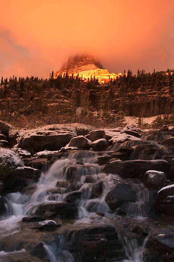 Glacier National Park Montana. Clements in morning alpenglow, first snow, high alpine creek. Fall Montana.