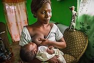 In the Ghanan community of Nyamebekyere, Julliet Donkov breastfeeds her young baby. Nurses were recently assigned to the area to help with local health care needs.