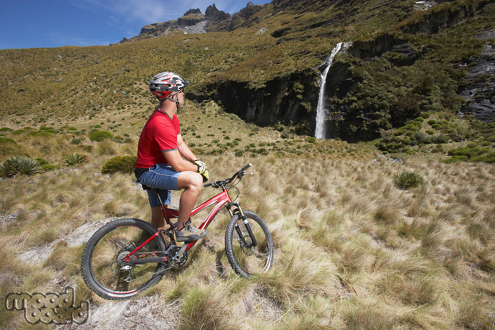 Cyclist looking at waterfall in field