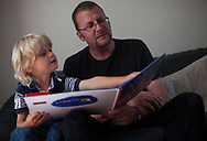 Damien (39) reads to Regan (5 ) at home in Shefield UK Tuesday, Aug. 12, 2014The D'Arby family is involved in the FAST  (Families and Schools Together) program which encourages parents to read to their children at home.(Elizabeth Dalziel for Save the Children )