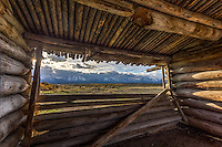 The window view of the Teton Mountain Range in Grand Teton National Park as seen from the center room of Cunningham Cabin, an old log cabin from the early settlers to the park.