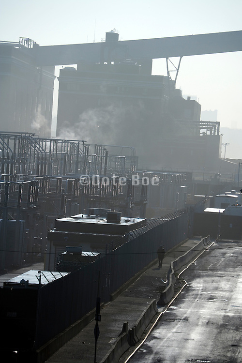 electric power plant with one person walking seen in early morning light