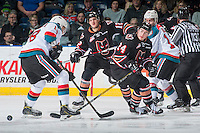 KELOWNA, CANADA - FEBRUARY 1: Luke Coleman #24 of the Calgary Hitmen passes the puck between the legs of Carsen Twarynski #18 of the Kelowna Rockets on February 1, 2017 at Prospera Place in Kelowna, British Columbia, Canada.  (Photo by Marissa Baecker/Shoot the Breeze)  *** Local Caption ***