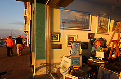 KNOKKE, BELGIUM - JULY-24-2005 -  An artists paints in her gallery on the water front in Knokke. (Photo © Jock Fistick)
