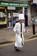 A young boy dressed as a Purim Rabbi in white robes and a white tall furry hat crosses Dunsmure road by a local chemist during the festival of Purim.