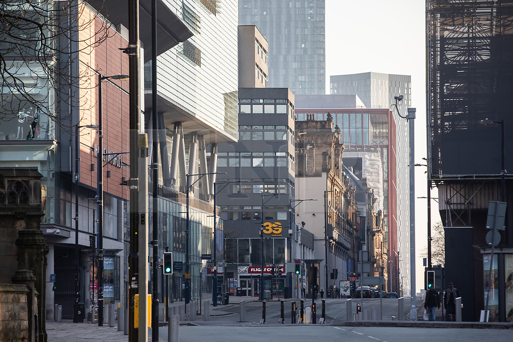 © Licensed to London News Pictures. 26/03/2020. Manchester, UK. Manchester City Centre lies nearly empty during a sunny spring afternoon . The British government has imposed a lockdown on all but essential activities and instructed people to reduce social contact as part of quarantine measures to prevent the spread of Coronavirus ( COVID-19 ) . Photo credit: Joel Goodman/LNP