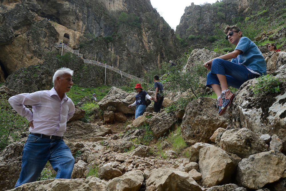 Christian pilgrims climbing a mountain path to the Rabban Beya Temple. The 4th century Christian monastery is a series of monastic caves carved into a mountain high above the Shaqlawa valley and an important pilgrimage site for the Assyrian community. Shaqlawa, Iraq. 22/04/2014.