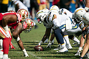 Los Angeles Chargers center Mike Pouncey (53) gets set to snap the ball with the Chargers offensive line at the line of scrimmage opposite the San Francisco 49ers defensive line during the NFL week 4 regular season football game against the San Francisco 49ers on Sunday, Sept. 30, 2018 in Carson, Calif. The Chargers won the game 29-27. (©Paul Anthony Spinelli)