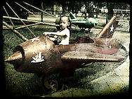 Two Vietnamese boys play in the old metal planes of a park ride in Hanoi, Vietnam, Southeast Asia
