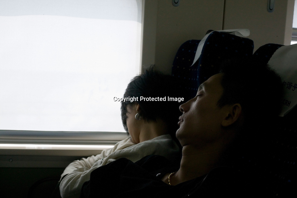 Beijing, September 11 , 2011 : passengers doze off during the train ride to Shanghai. The passenger-dedicated trunk line opened in June 2011, reducing the 1,318 km journey between Beijing and Shanghai to less than 5 hours. Trains reach top speeds of 300 km/h (186 mph) for the entire trip.