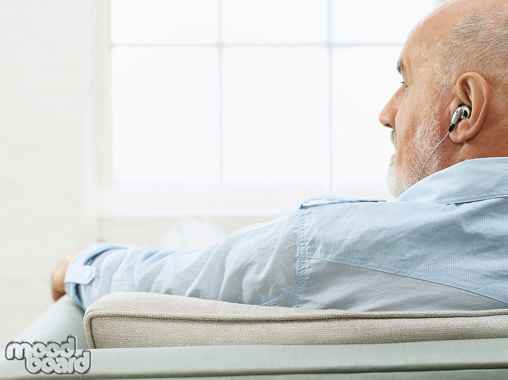 Middle-aged man wearing earphones sitting on sofa and looking to side back view