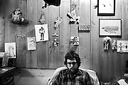Sean, in his room in Harmony residence.  The wall behind him is decorated with some examples of his artwork.  His work has been exhibited in galleries throughout Virginia.  Members like in dormitory-style residences named after former intentional communities, and Harmony refers to a 19th Century American utopian society.