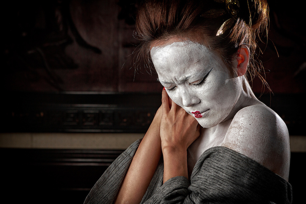 Woman with traditional Japanese white face makeup.