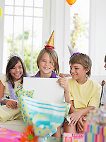 Chlidren (7-12) watching one boy open birthday presents