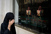 A Muslim lady wearing a Niqab passes the luxury shop window of Louis Vuitton featuring their exclusive range of bags with the face of Leonardo da Vinci's Mona Lisa - a collaboration with the artist Jeff Koons and part of work entitled The Masters Collection, on 5th July 2017, on New Bond Street, in London England.