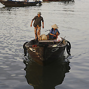 A boat heads to the early morning fish market in Hoi An, Vietnam.