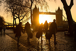 © Licensed to London News Pictures. 16/12/2018. London, UK.  People walk along the River Thames path next to Tower Bridge as the sun rises this morning following a cold night in the capital.  Photo credit: Vickie Flores/LNP