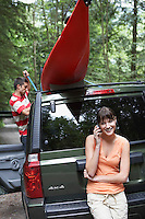 Woman using mobile phone by car man tying kayak on roof in forest