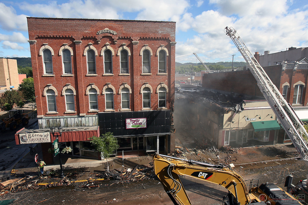 9/13/13--Winona<br /> Rubble litters the street after fire crews had to destroy the historic building that housed the Islamic Center of Winona, right, Friday, Sept. 13, 2013. The building on the left was saved, however. The fire destroyed three buildings and forced officials to evacuate the entire block. (Photo for MPR News by Alex Kolyer)