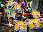 03 SEPTEMBER 2016 - BANGKOK, THAILAND:   Pom Mahakan resident hold up portraits of Bhumibol Adulyadej, the King of Thailand, while they block an alley in their community. Hundreds of people from the Pom Mahakan community and other communities in Bangkok barricaded themselves in the Pom Mahakan Fort to prevent Bangkok officials from tearing down the homes in the community Saturday. The city had issued eviction notices and said they would reclaim the land in the historic fort from the community. People prevented the city workers from getting into the fort. After negotiations with community leaders, Bangkok officials were allowed to tear down 12 homes that had either been abandoned or whose owners had agreed to move. The remaining 44 families who live in the fort have vowed to stay.    PHOTO BY JACK KURTZ