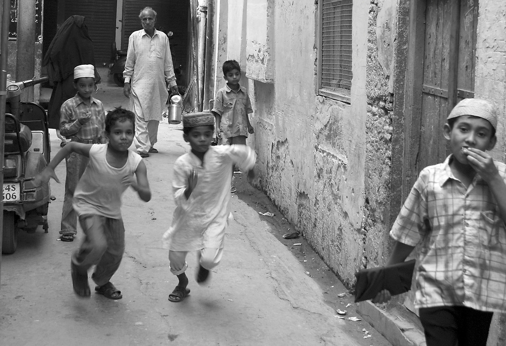 Kids running down a street in Old Delhi, India