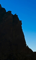 Climbers rappeling and scrambling down from a rock climb on one of the many rock walls at Smith Rock State Park, Oregon, USA.