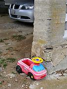 Männerspielzeug: Spielzeugauto aus Plastik und BMW in Garage. Jouet pour machos: voiture en plastique et grand BMW. Toys for men: plastic toycar and big BMW.  © Romano P. Riedo