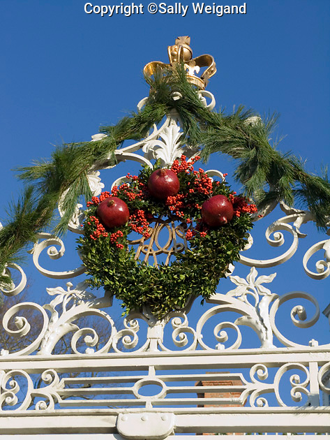 top of white iron gate; Governor's Palace; Christmas decorations; garland; wreath; close up; Colonial Williamsburg; Virginia; Virginia; winter
