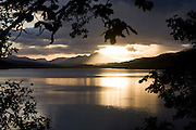 A strong evening sun sinks below storm clouds and Highland mountains at Loch Garry, Glengarry, Scotland. .